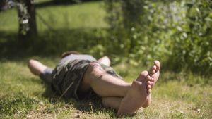 Mies loikoilee nurmikolla.