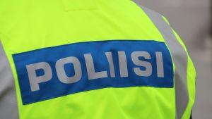 Poliisi-teksti poliisin huomioliivissä.