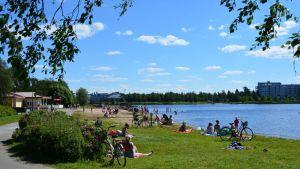 Auringonottajia Oulussa Tuiran uimarannalla.