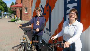 Nuori mies ja nainen hymyilevät sähköpyörien kanssa oranssivankoisen kontib edessä.