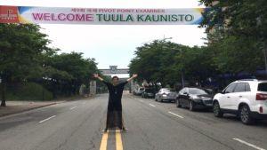Tuula Kaunisto seisoo Etelä-Koreassa kadulla, jonka ylittää tervetulobanderolli, jossa tekstinä Welcome Tuula Kaunisto.