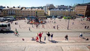 Turistit ottavat ryhmäkuvaa tuomiokirkon portailla.
