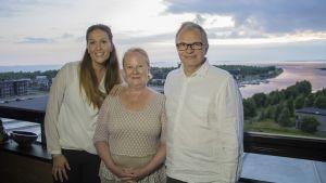 Toimittaja Sanna Kähkönen seisoo Tuula ja Pertti Markkulan kanssa pariskunnan parvekkeella.