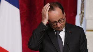 Kuvassa Ranskan presidentti François Hollande suhii oikealla kädellään hiuksiaan.