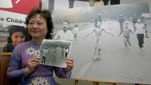 Kim Puc pitää kädessään kuvaa itsestään ja muista juoksevista lapsista, joiden takana kävelee Yhdysvaltain sotilaita. Taustalla on suurennos kuvasta.