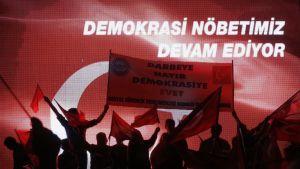 Ihmisjoukko heiluttaa Turkin lippuja ja pitelee hallitusta tukevaa kylttiä.