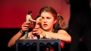 Pikkutyttö leikkii nukeilla.