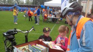 Lapset katsovat kirjastopyörän kirjoja.