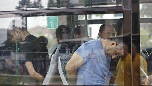 pidätettyjä miehiä bussissa