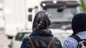 Kaksi huivitettua naista odottaa pääsevänsä tien yli.