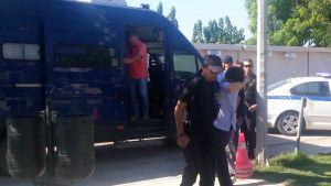 Siviiliasuinen mies kävelee pitäen kättä kasvojensa peittona. Hänen vieressään kulkee poliisi.