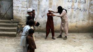 Isis-sotilas opettaa lapsia aseenkäytössä Kunarin provinssissa Afganistanissa 30. heinäkuuta 2015.