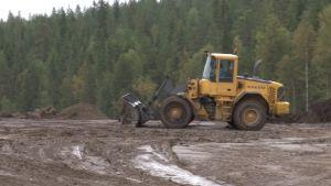 Kauhakuormaaja tasoittaa maata maanläjitysalueella.