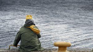 Nainen istuu veden ääressä.