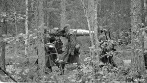 Haavoittunutta sotilasta kannetaan maastossa