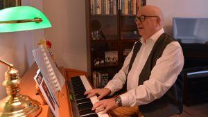 Mies soitaa pianoa ja laulaa.