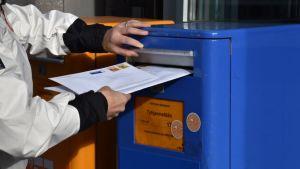 Nainen laittaa kirjeitä postilaatikkoon.