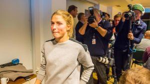 Therese Johaug saapuu dopingkäryään käsittelevään lehdistötilaisuuteen. Valokuvaajat ottavat taustalla kuvia Johaugista.