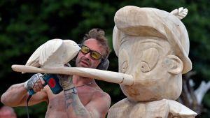 Paidaton mies työstää suurta puista Pinokkio-veistosta.