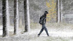 Nuori mies kävelee lumisateessa.