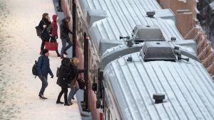 Matkustajia nousemassa junaan.