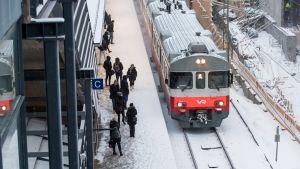 Matkustajia odottamassa junaa.