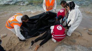 Libyan Punaisen Ristin edustajat peittävät Välimereen hukkuneen siirtolaisen ruumiin Libyan rannikolla.