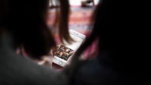 Nuoret selailevat kännykkäkuvia.