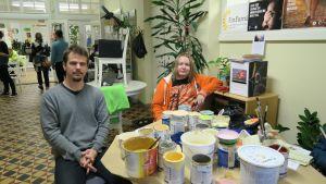Kaksi miestä istuu kahvilan pöydässä maalipurkkeja edessään