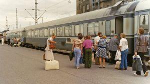 Kuvassa matkustajat nousevat junaan asemalaiturilla Helsingissä 1976