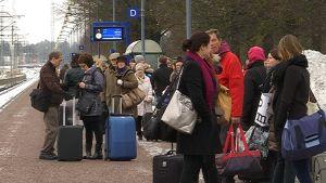 Matkustajia odottamassa junaa asemalla