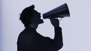 Mies huutaa megafoniin