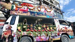 Kuvassa kaksi apinaa syömässä hedelmiä pakettiauton lavalla. Useampia apinoita on asfaltilla auton vieressä istumassa.