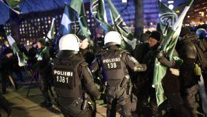 Poliisit keskustelevat Pohjoismaisen vastarintaliikkeen kannattajan kanssa.