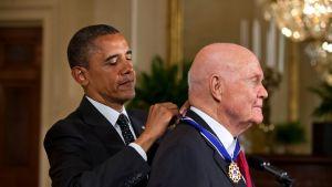 Mies asettaa kunniamitalia toisen miehen kaulaan.