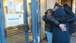 Sangar, Kristina ja Harri halaavat vastaanottokeskuksen ovella