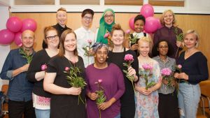Reilun kymmenen henkilön ryhmä ruusut käsissään.