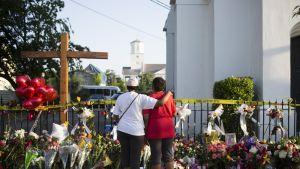 Kaksi ihmistä seisoo kirkon edustalla aidan luona. Aidan luo on tuotu suuri määrä kukkia. Aitaa pitkin kulkee poliisin keltainen huomionauha.