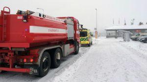 Pelastuslaitoksen auto ja ambulanssi Terrafamen portilla.
