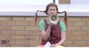 Kirjastonhoitaja Arja Palonen pukeutuneena Peppi Pitkätossuksi. Kädessään megafoni.