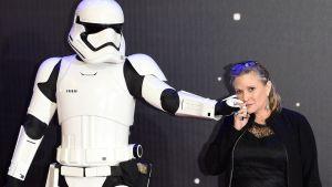 Mustaan pukeunut nainen pitää valkoisen Stormtrooper elokuvahahmon kättä poskellaan.