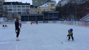 Äiti ja poika jääkiekkokentällä Tampereen koulukadulla.