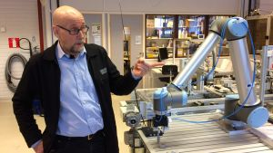 Jarmo Happonen robotin seurassa Kajaanin ammattikorkeakoululla.