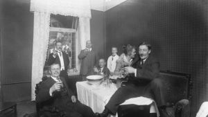 Naiset ja miehet juovat kabinetissa alkoholia