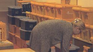 Porin kaupunginkirjaston logistiikkajohtaja Minna Kataja pakkaa kirjoja Postin laatikoihin.