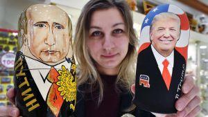 Myyjä esittelee Putinin ja Trumpin näköisiä puunukkeja lahjatavarakaupassa Moskovassa.