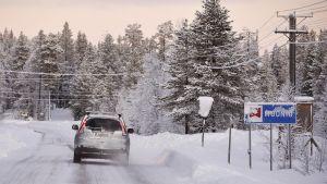 Auto liikenteessä lumisessa maisemassa Muoniossa.