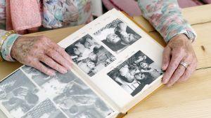 Iäkäs nainen katselee valokuvia.