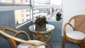 tuoleja, pöytä ja kukkasia parvekkeella