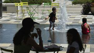 Lapset leikkivät kuumana kesäpäivänä Dallasissa suihkulähteessä.